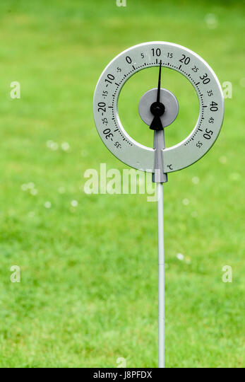 Circular garden thermometer, which measures temperature in degrees centigrade, stuck in a lawn. - Stock Image