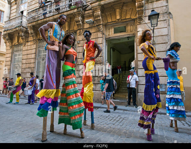 Horizontal portrait of stilt walkers posing for a photograph in Havana, Cuba. - Stock Image