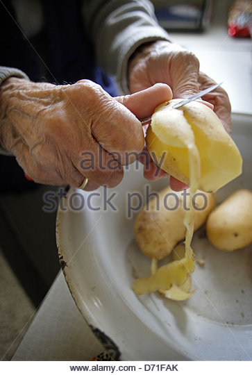 Senior woman peeling potatoes in a kitchen - Stock-Bilder