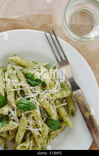 Pasta with Pesto on White Plate with Fork - Stock Image