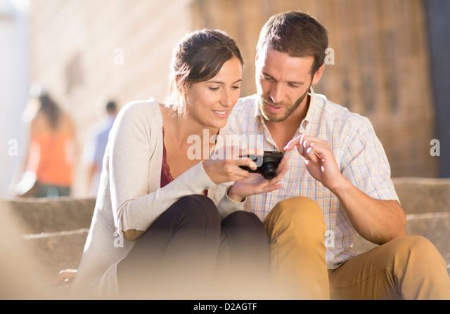 Couple looking at pictures on camera - Stock Image