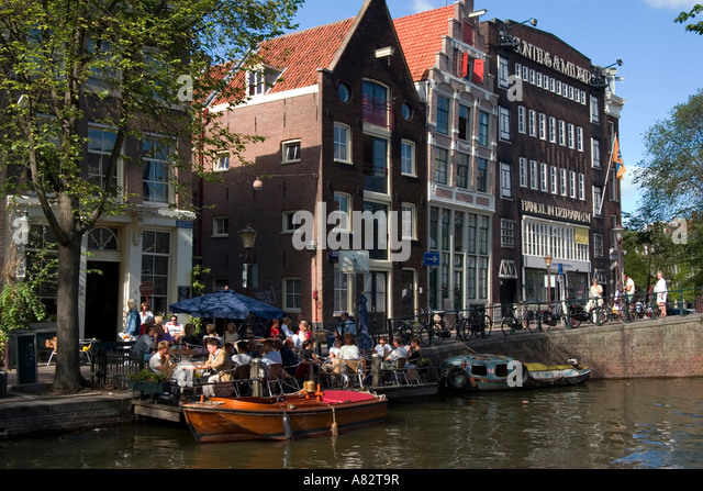 Amsterdam street cafe at a canal typical architecture - Stock Image