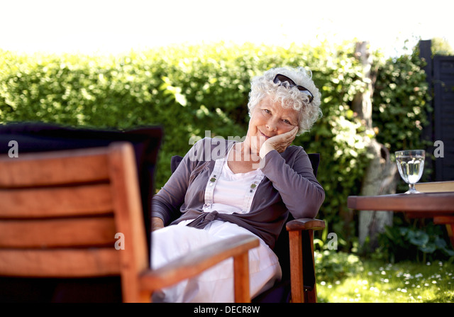 Old woman sitting on chair looking at camera. Senior female relaxing in backyard garden enjoying her retirement - Stock Image