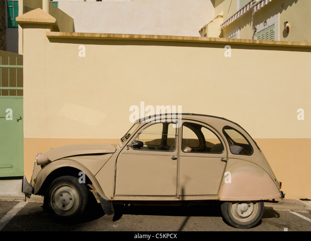 An old beige Citron Deux Chevaux car parked by a matching wall, Servian, France - Stock Image