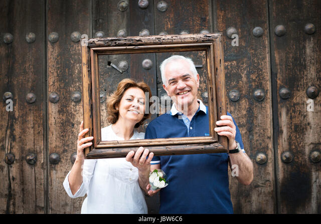 Portrait of senior couple, holding wooden frame in front of their faces, Mexico City, Mexico - Stock-Bilder