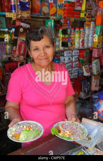 Lima Peru Surquillo Mercado de Surquillo market stall business shopping vendor grocer Hispanic woman senior holding - Stock Image