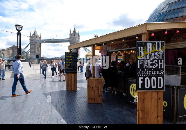 A food stall on the walkway on the south bank of the Thames London Bridge is in the background. - Stock Image