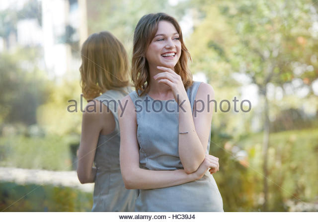 Young woman standing in front of reflective window. - Stock Image