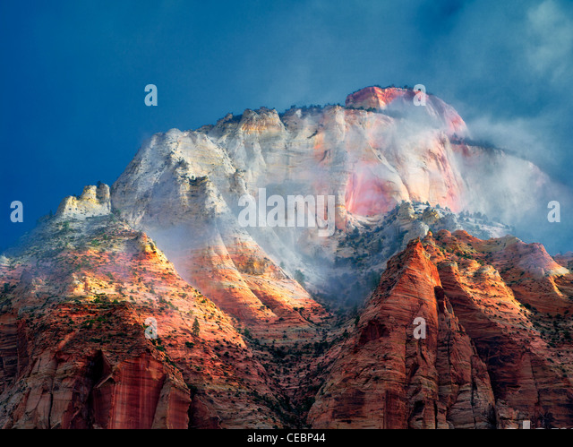 Sun peaking through storm clouds at East Temple. Zion National Park, Utah - Stock Image