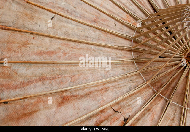 Old paper umbrella. It has a crane motif on oiled paper and the umbrella is constructed of bamboo and string. - Stock Image