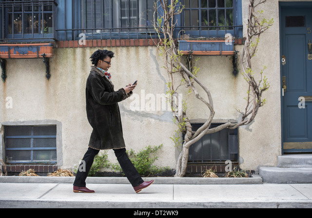 A woman in a warm coat walking along the street checking her phone - Stock Image