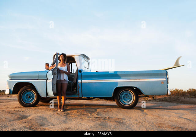 Portrait of young female surfer leaning on pick up truck door, Leucadia, California, USA - Stock Image