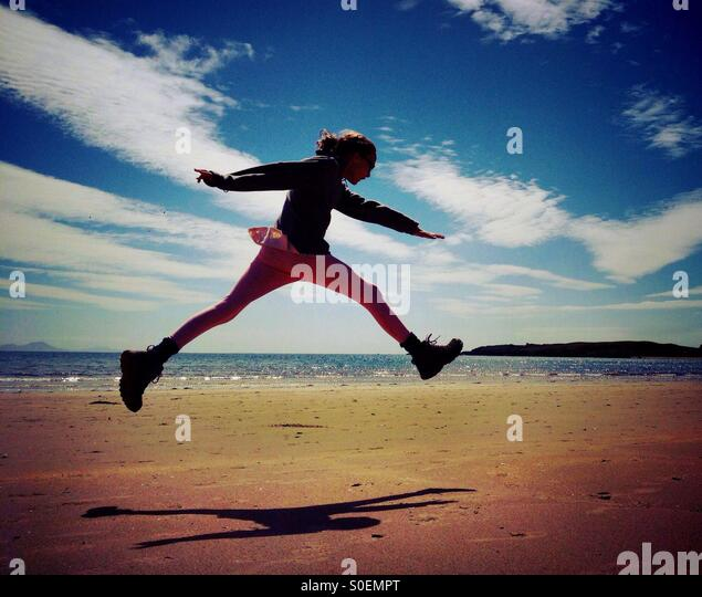 Young girl leaping for joy on Newborough beach on Anglesey - Stock Image
