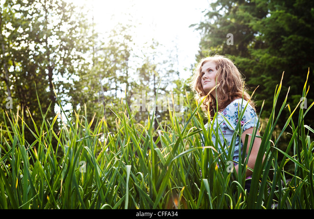 A teenage girl looking into the distance in a organic garden in Idaho. - Stock Image