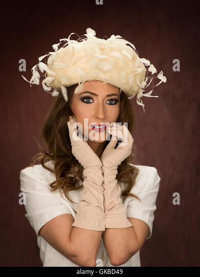 Young brunette woman modeling a vintage white hat and gloves - Stock Image
