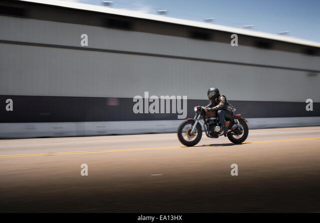Blurred image of speeding male motorcyclist - Stock-Bilder