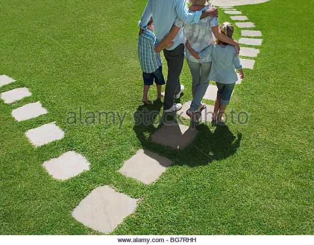Family walking on stones in grass - Stock-Bilder