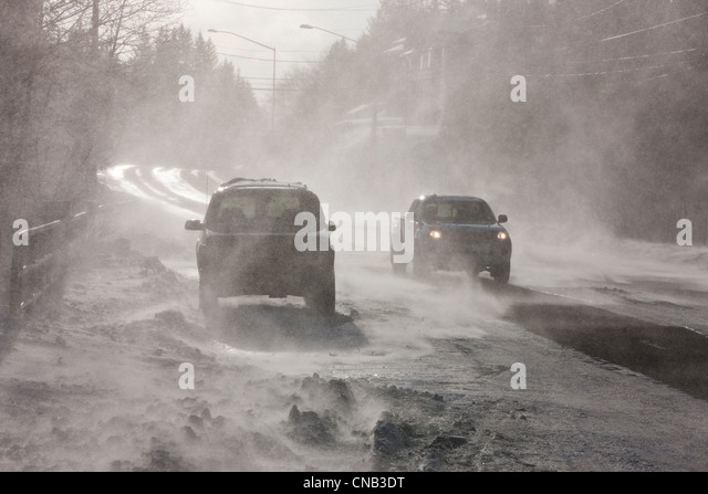 Vehicles drive on Douglas Roadway obscured by 70 mph blowing wind and snow, Juneau, Southeast Alaska, Winter - Stock Image