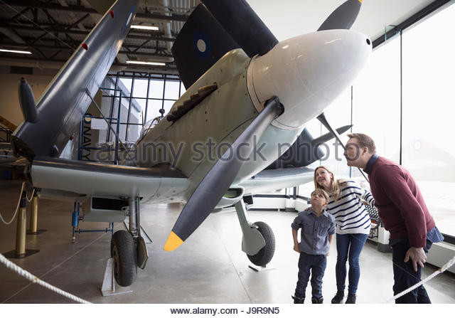Curious family viewing propellor on airplane in warm museum hangar - Stock-Bilder
