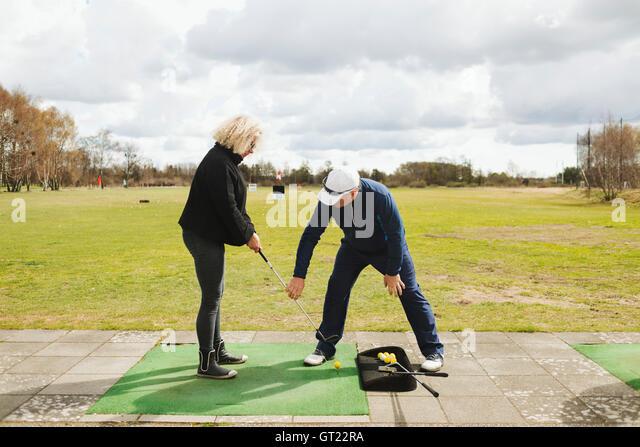 Man teaching golf to woman at driving range - Stock-Bilder