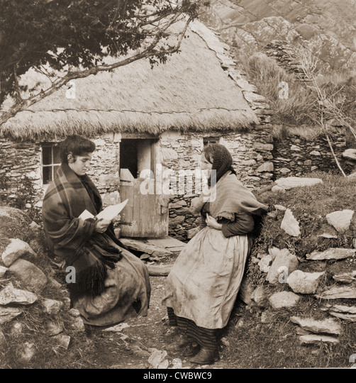 A LETTER FROM PAT IN AMERICA. Young Irish woman reading a letter from a relative  in America to an older woman outside - Stock-Bilder