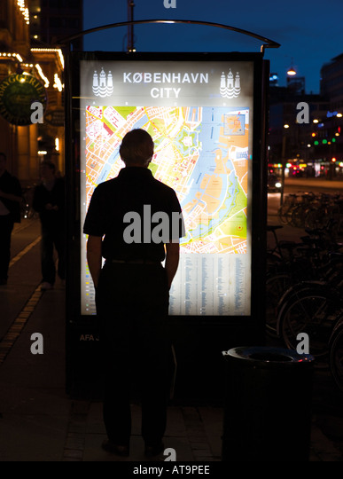 Copenhagen Denmark Silhouette of tourist examining city map - Stock Image