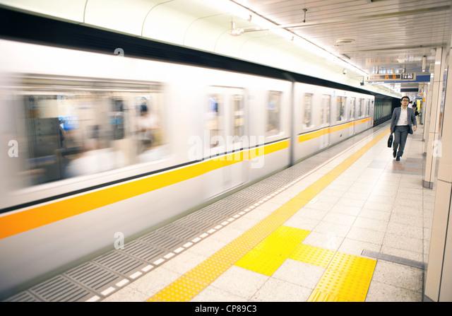 Man walking on platform of a Tokyo subway station, Japan. - Stock Image
