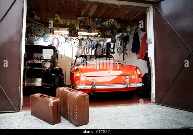 Vintage car and trunk suitcases in garage - Stock Image