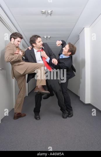 Businessmen fighting in corridor - Stock Image