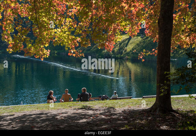 A group of people sitting on the grass, in front of the beautiful lake, in fall, in Lafontaine Park in Montreal - Stock-Bilder