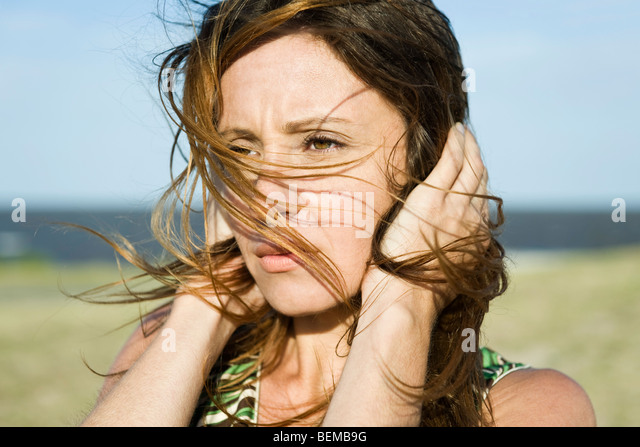 Woman standing in wind, hands holding hair down, close-up - Stock Image