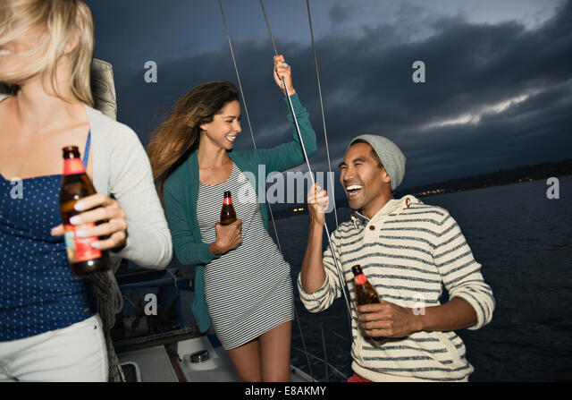 Friends on sailing boat with beer - Stock Image