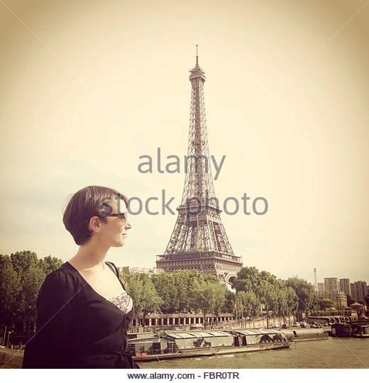 Young Woman In Front Of Eiffel Tower And Clear Sky - Stock Image