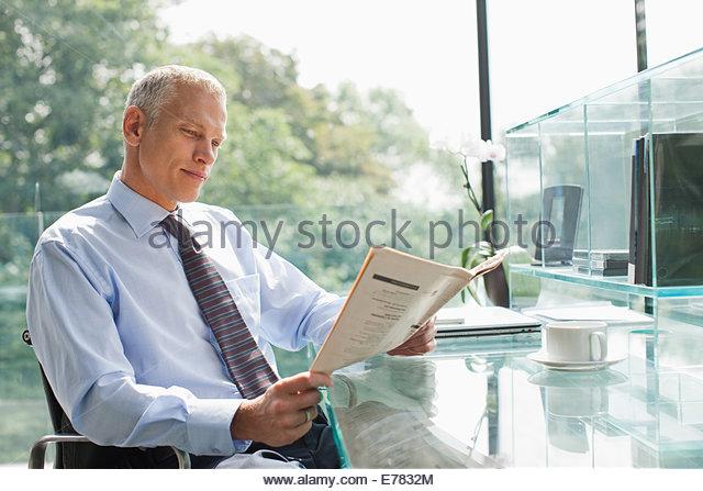 Businessman reading newspaper at desk - Stock Image
