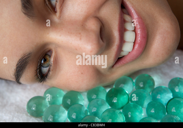 Close up of woman with glass beads - Stock Image