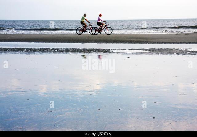 South Carolina Hilton Head Island Sea Pines Plantation Atlantic Ocean resort man woman couple retirees bicycle cycling - Stock Image