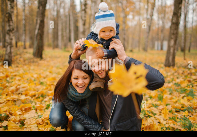 Middle Eastern couple carrying baby son in park in autumn - Stock Image
