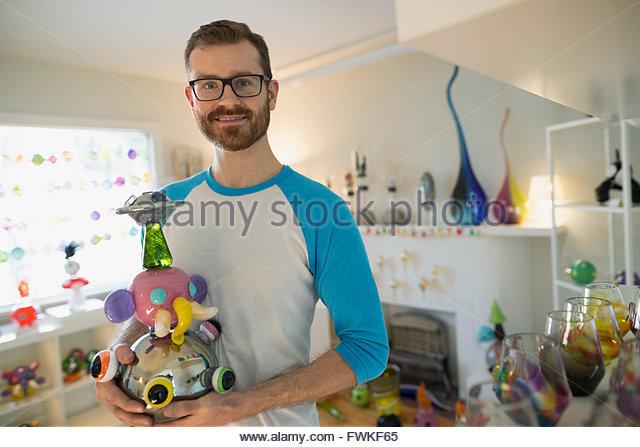 Portrait confident glassblower holding creative piece retail shop - Stock Image
