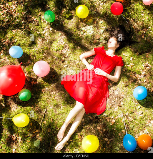 United Kingdom, England, Berkshire, Young woman with balloons sleeping in forest - Stock Image