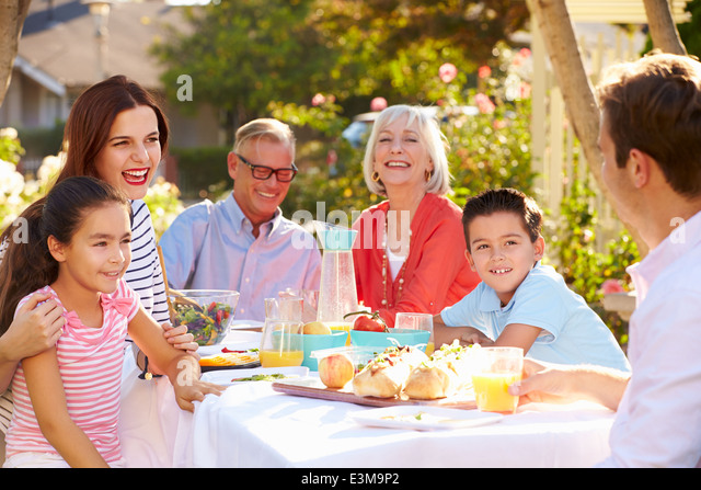 Multi-Generation Family Enjoying Outdoor Meal In Garden - Stock Image