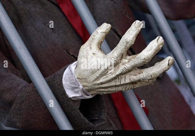 Hand reaching through prison bars, haunted house figure - Stock Image