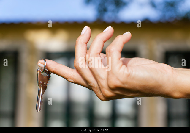 Woman's hand holding key, cropped - Stock-Bilder