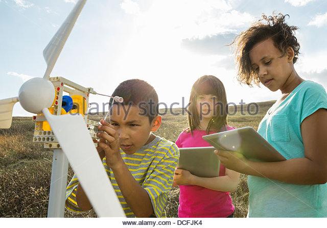 Schoolchildren analyzing wind turbine model outdoors - Stock Image