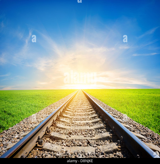 Railway to the sun through green field - Stock Image