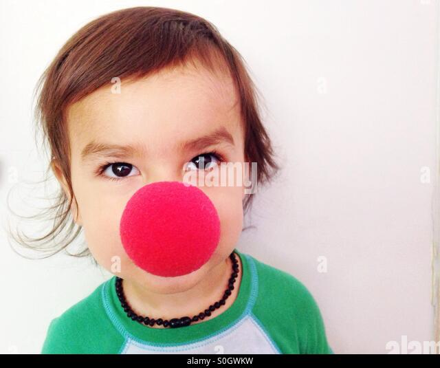 Cute toddler with red clown nose - Stock Image