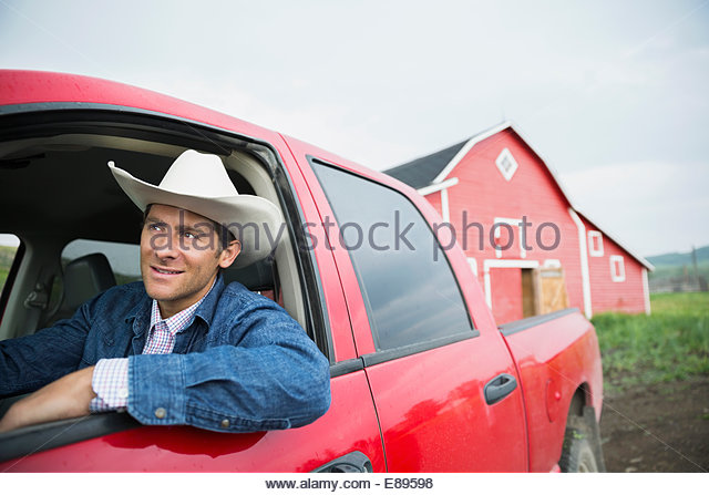 Rancher with cowboy hat driving truck - Stock Image