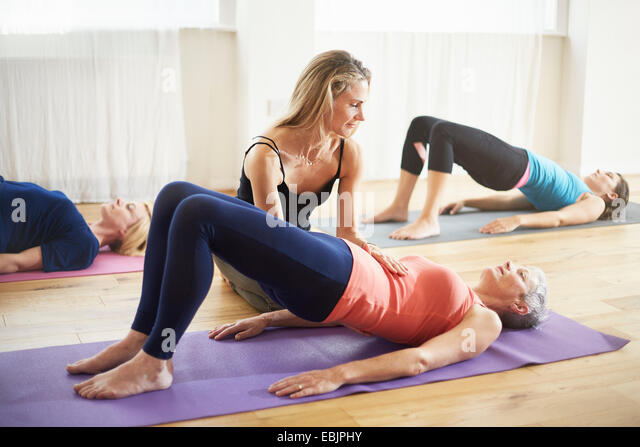 Teaching supporting student lying on back in pilates class - Stock Image