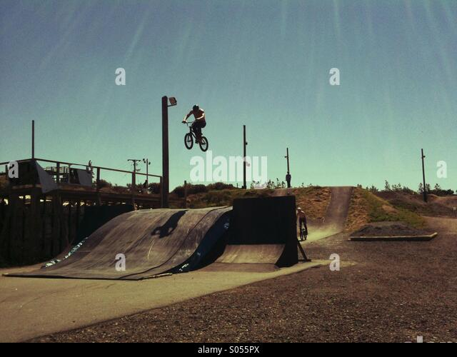 BMX rider jumping at a track in the sun - Stock Image