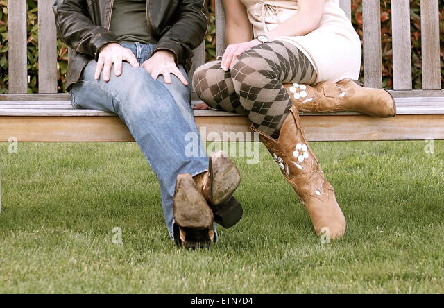Low section of a couple wearing cowboy boots sitting on a bench - Stock-Bilder
