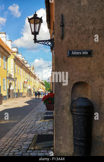 The facade of the barracks on the street Jacob Aldar mounted in the wall of old cannon in Riga sunny summer day - Stock Image